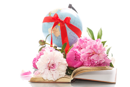 book with blooming peonies and globe on white background photo