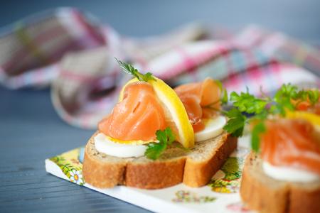sandwich with salted salmon, egg and lemon photo
