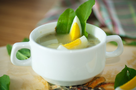 sour grass: sorrel soup in a bowl with egg