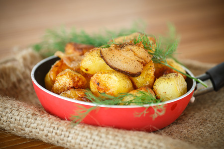 fried potatoes with slices of bacon in a frying pan photo