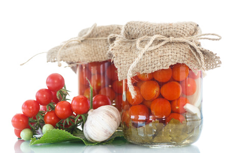 tomatoes marinated in jars with spices on a white background photo