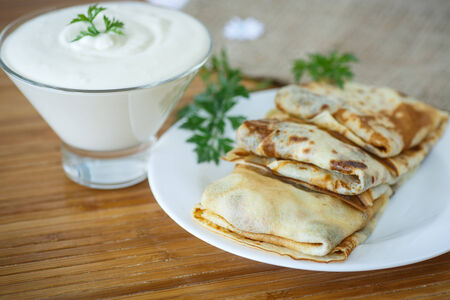 traditional pancakes wrapped inside with meat on the plate photo