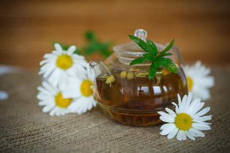 treatment with chamomile tea on wooden table photo