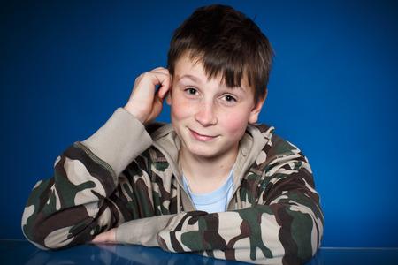 cute happy teenager boy on a blue  photo