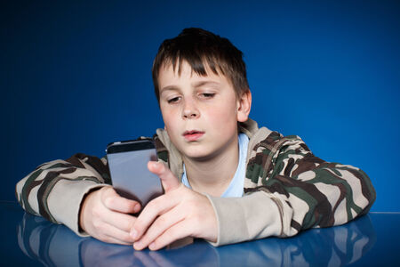 teenage boy with phone in hand on blue  photo