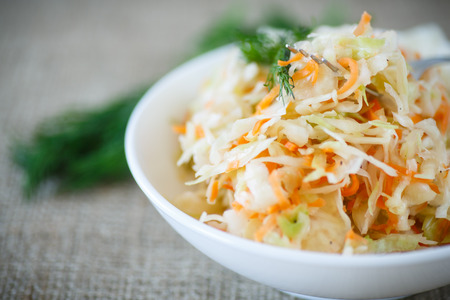 pickled cabbage and carrots in a white plate on the table