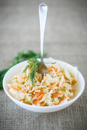 ingelegde kool en wortelen in een witte plaat op de tafel