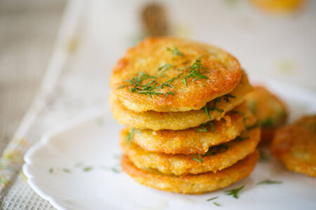 fried potato pancakes with dill on white plate photo
