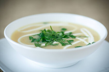 puree soup with greens and sour cream in a white plate photo