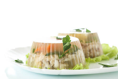 Jellied fish with egg and vegetables on a white background photo