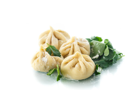 traditional raw manti with meat inside on a white background