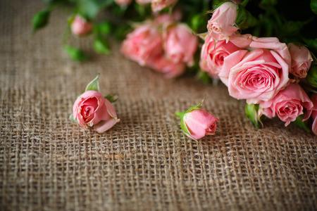 hermoso ramo de rosas de color rosa en una vieja mesa de arpillera