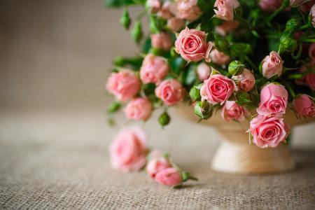 mooi boeket van roze rozen op een oude tafel van jute Stockfoto