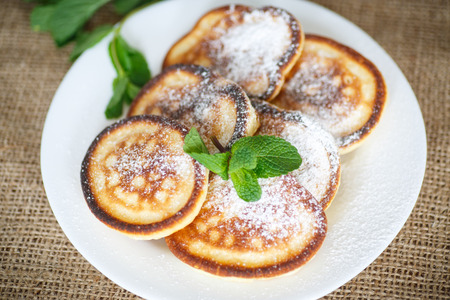 powdered sugar: sweet pancakes with powdered sugar and a sprig of mint