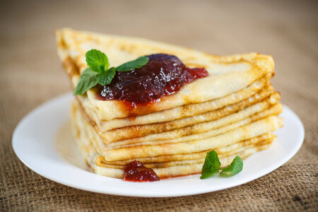 many thin pancakes with jam on the table photo