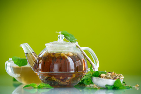 green tea in a glass pot on a green background photo