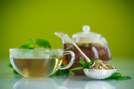 tea kettle: green tea in a glass pot on a green background