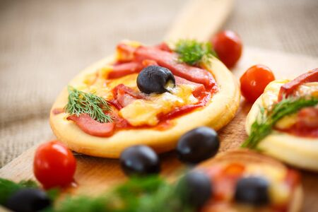 mini pizza: mini pizza with olives, bacon and cheese