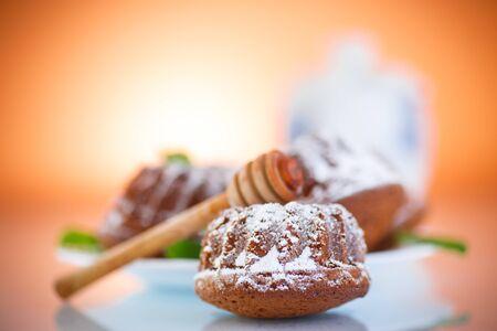 sweet honey muffins in powdered sugar on orange background photo