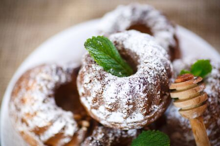 sweet honey muffins in powdered sugar on the table photo