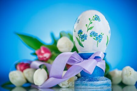 Decorative easter egg with a bouquet of spring tulips on a blue background photo