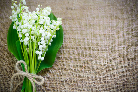 bouquet of lily of the valley flowering in the table of burlap Stock Photo