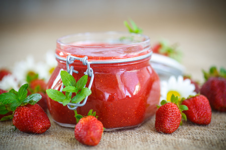 jam jar: strawberry jam in a glass jar with strawberries on a table