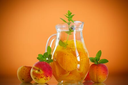decanter: apricot compote in a glass decanter on an orange background Stock Photo