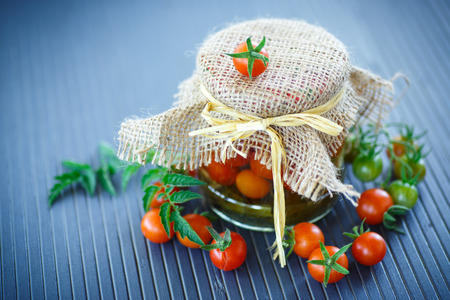 preserve: tomatoes marinated in jars with spices on a wooden table