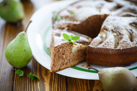 pear: cake with pears in powdered sugar on a wooden table