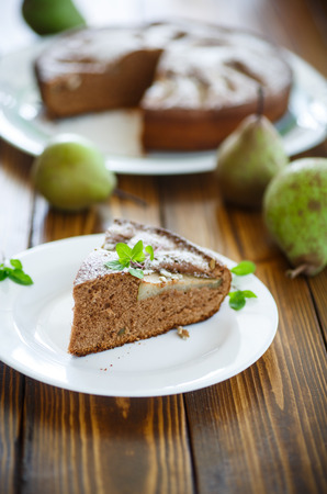 powdered sugar: cake with pears in powdered sugar on a wooden table