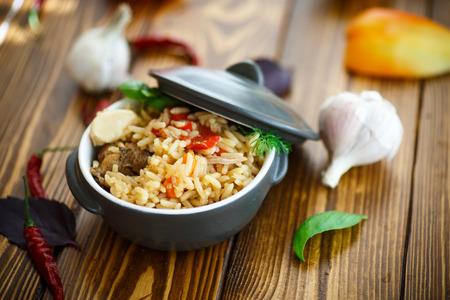 arroz blanco: pilaf de arroz y carne en un recipiente sobre una mesa de madera
