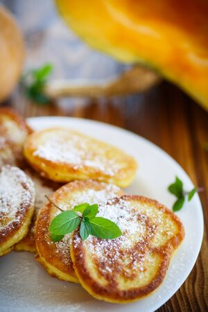 fucking: fried sweet pumpkin pancakes on a wooden table Stock Photo
