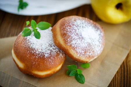 donuts with quince filling sprinkled with powdered sugar Stock Photo