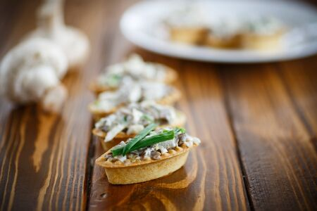 stuffing: tartlets with mushroom stuffing on the wooden table