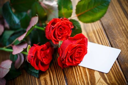text space: bouquet of red roses on a wooden table Stock Photo