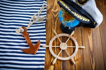 skipper: Decorative wooden steering wheel on an old wooden table Stock Photo