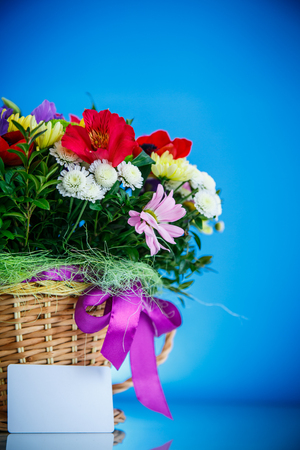 bouquet of spring flowers in a wicker basket on a blue background