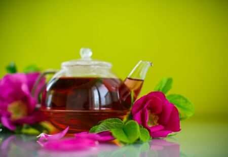 fresh tea with rosehip on a green background Banco de Imagens