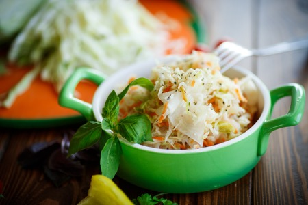 Sauerkraut with carrots in a bowl on a wooden table