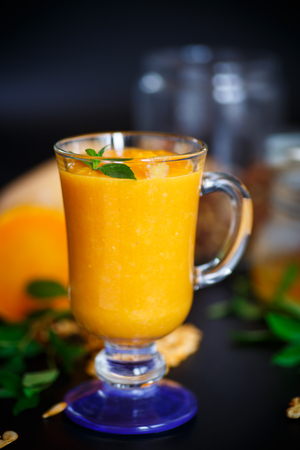 pumpkin smoothie with nuts and honey on a black background