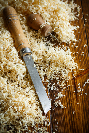 Woodworking tools. Chisel with sawdust on a wooden table Stock Photo