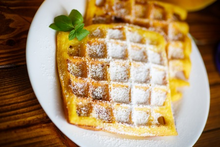sweet pumpkin waffles on the plate on a wooden table Stock Photo