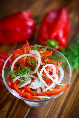 fresh salad with fresh peppers and onions on a wooden table Stock Photo