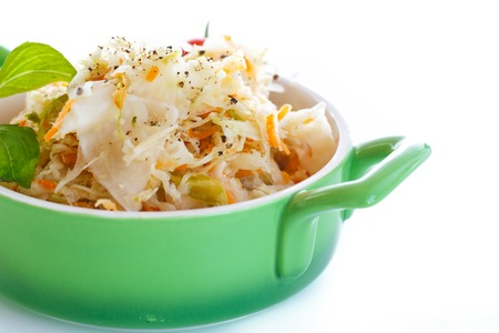 Sauerkraut with carrots in a bowl on a white background
