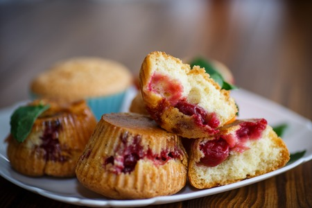 sweet muffins stuffed with cherries on a wooden table