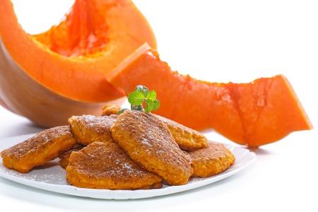 sweet pumpkin pancakeson a white background with a ripe pumpkin