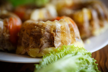 jellied meat with vegetables on a wooden table Stock Photo