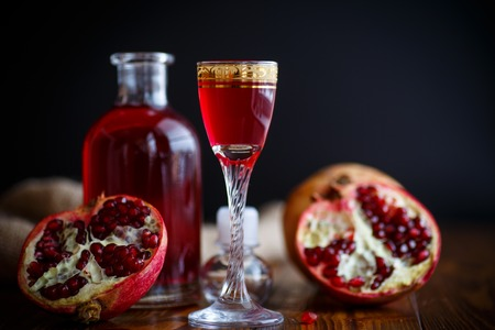 sweet pomegranate alcoholic cordial in the decanter with a glass Stock Photo