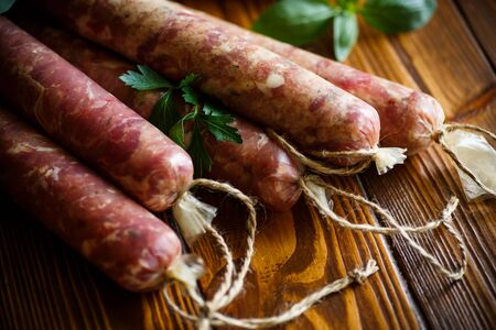 meaty: Raw organic homemade sausage made from natural meat on a wooden table Stock Photo